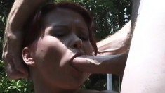 Wild redheaded chick takes in four guys' bulging cocks outdoors