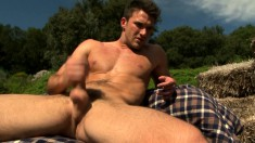 With the sun bathing his ripped body, a hunky stud makes himself cum