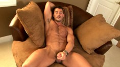 Horny tattooed stud gets naked on the couch to wank his boner